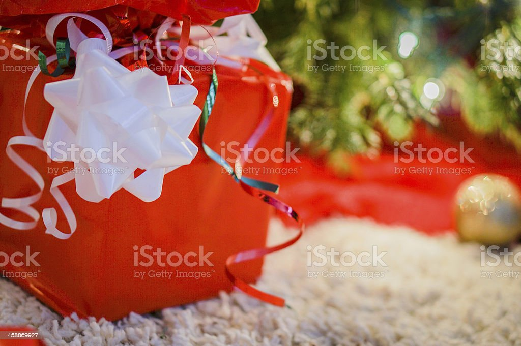 Red present with white bow near the christmas tree stock photo