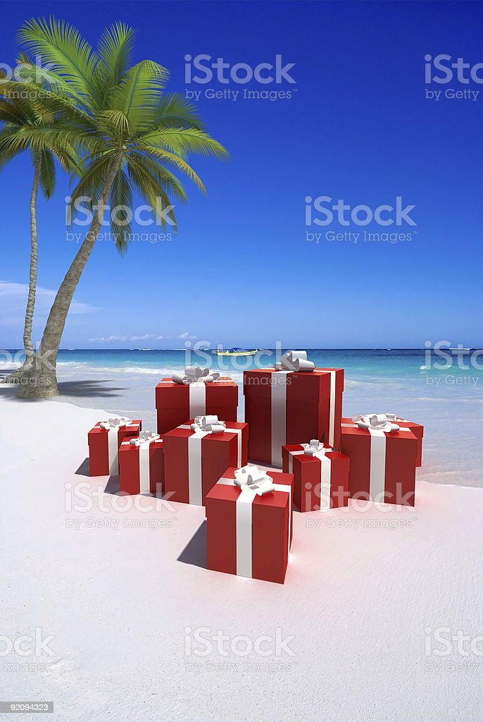 Red presents with white ribbon on a tropical beach stock photo