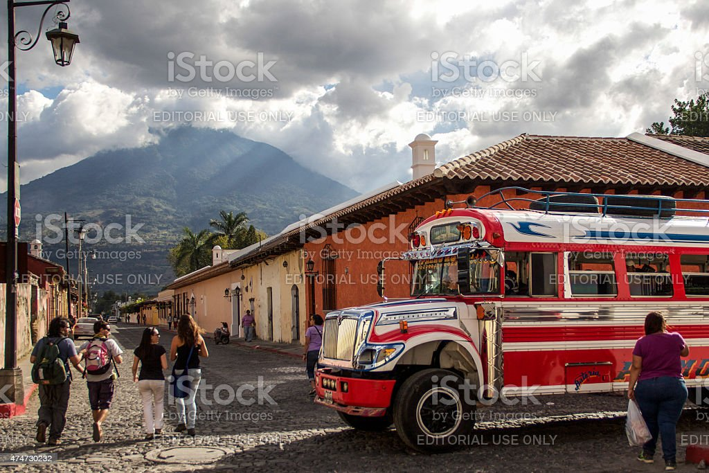 Red public bus and people walking in Antigua stock photo