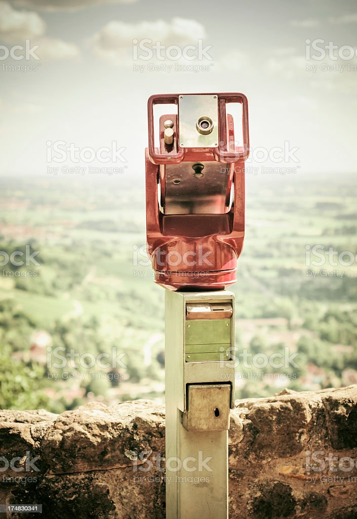 Red public telescope with defocused landscape royalty-free stock photo