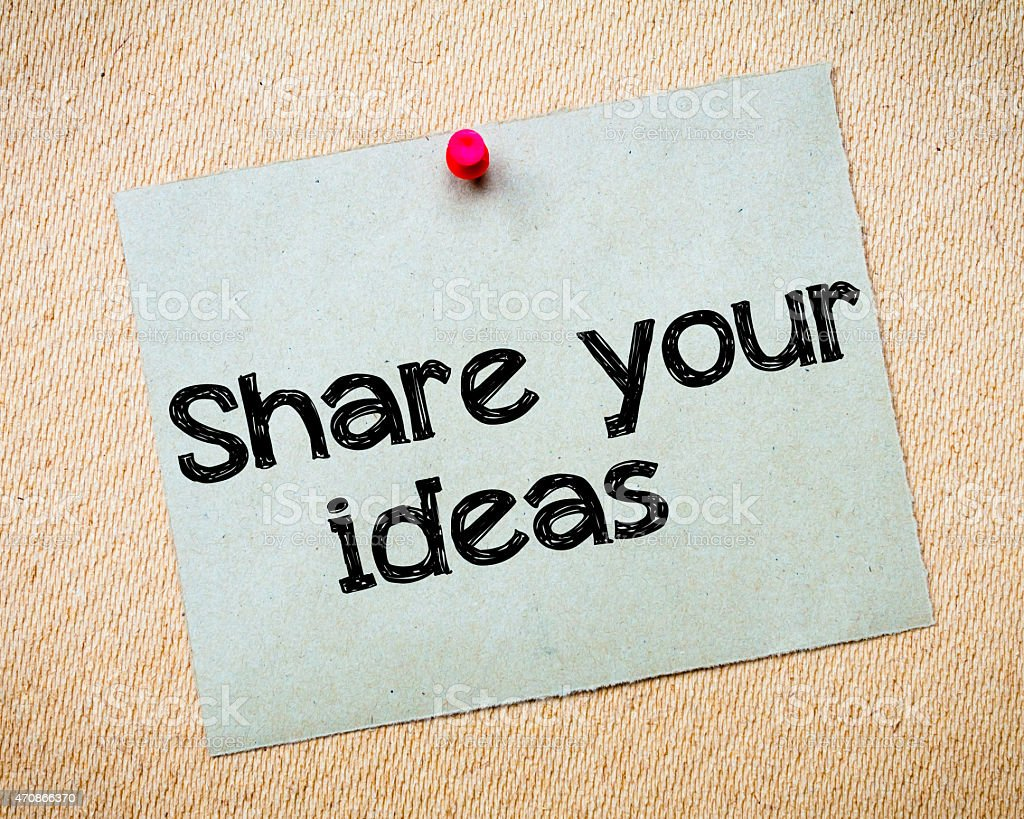 Red push pin holding share your ideas card in a place stock photo