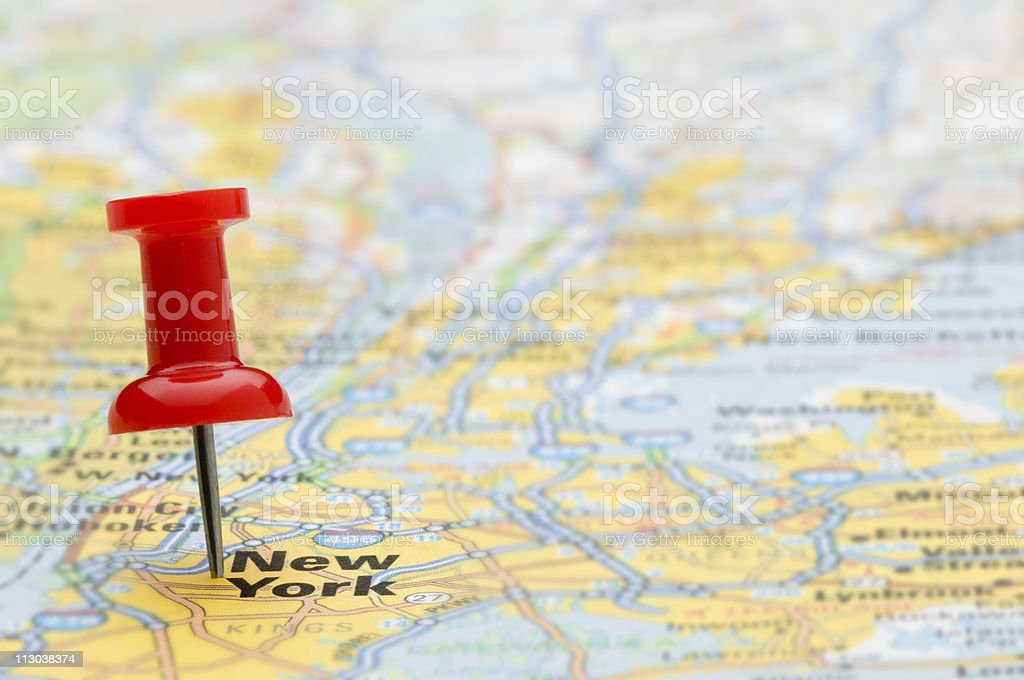 Red pushpin marking New York City on map, selective focus stock photo