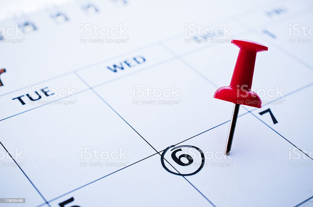 Red pushpin stuck in calendar on Wednesday the 6th royalty-free stock photo