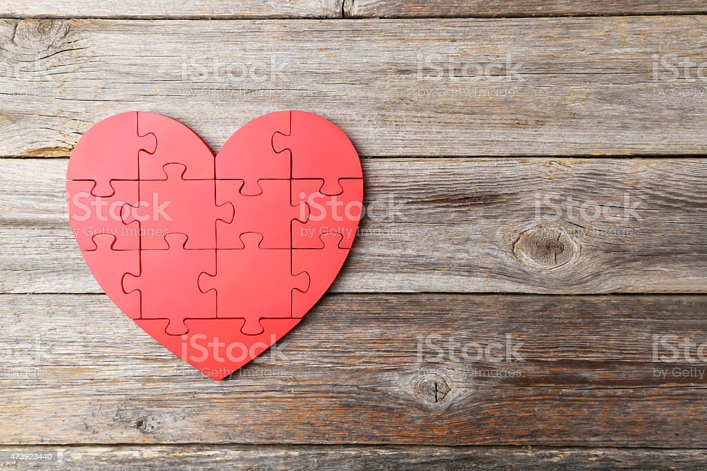 Red puzzle heart on grey wooden background stock photo