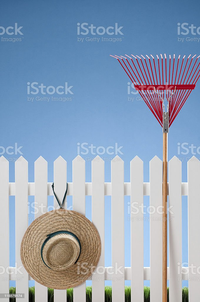 Red Rake And Hat On White Picket Fence royalty-free stock photo
