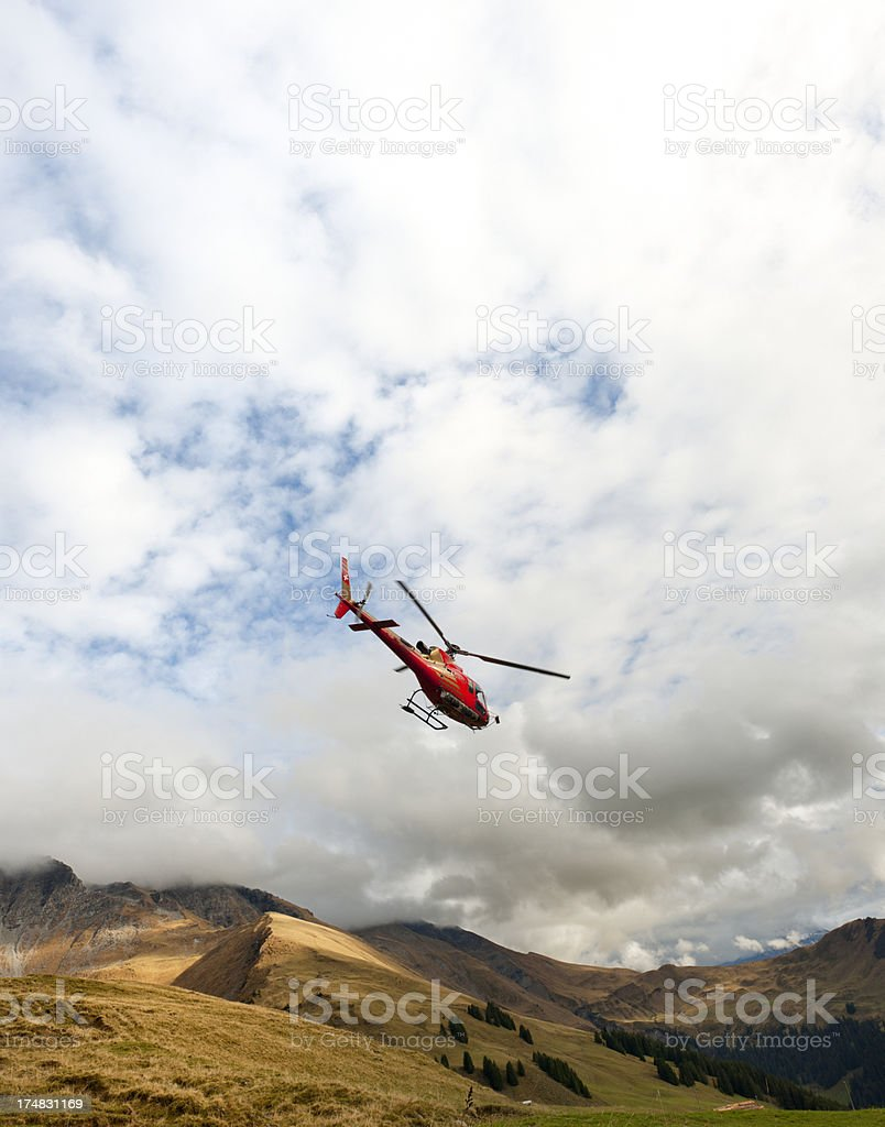 red rescue helicopter flying in valley royalty-free stock photo