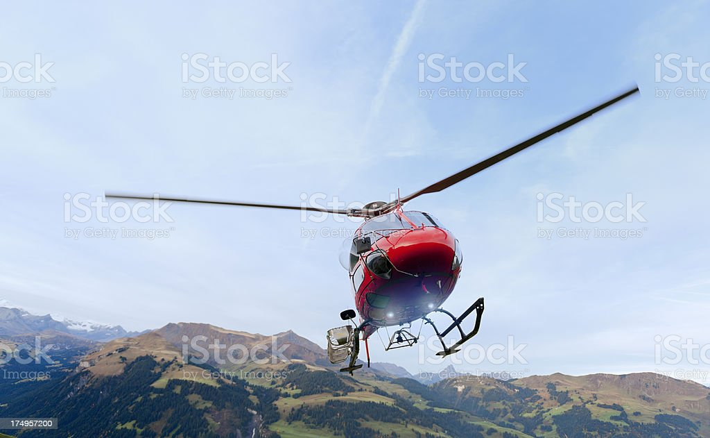 red rescue helicopter landing on mountain stock photo