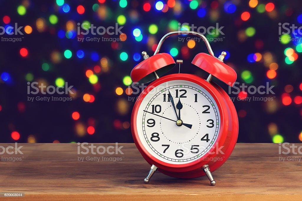 Red retro alarm clock at twelve o'clock stock photo