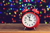Red retro alarm clock at twelve o'clock