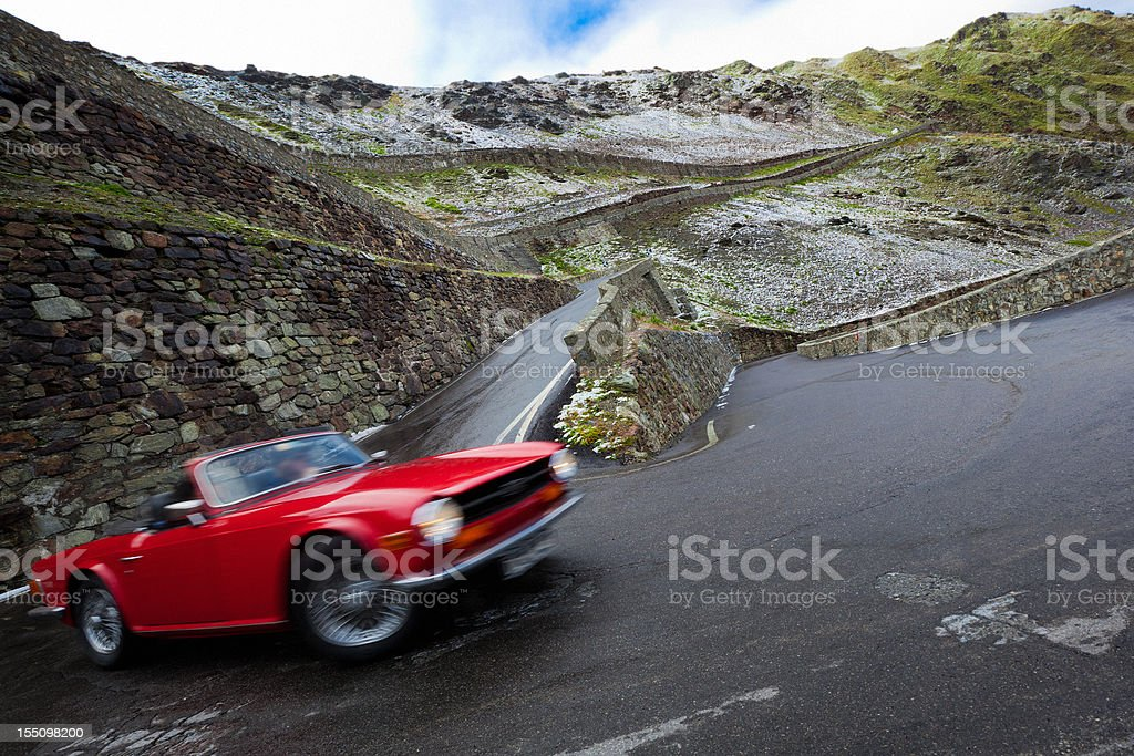 Red Retro Car Driving on a Mountain Road Roadtrip Travel stock photo