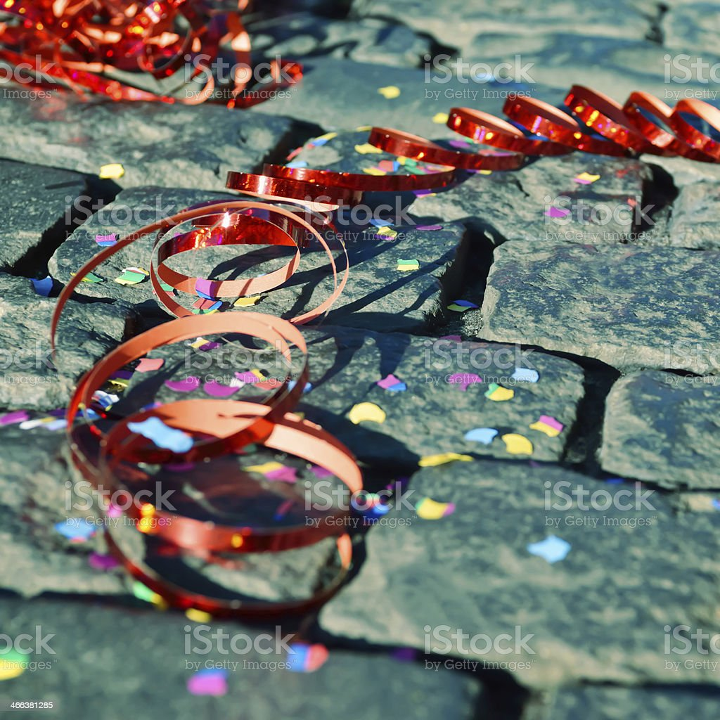Red ribbon and multicolor confetti on cobblestones for party stock photo