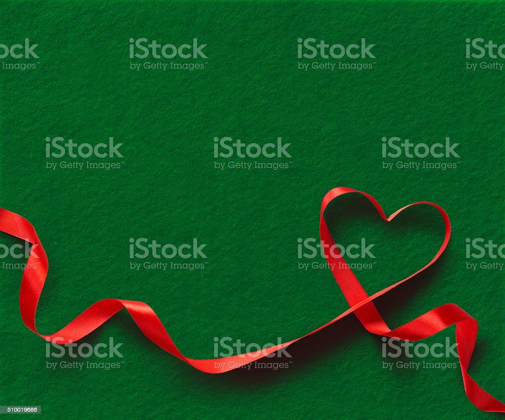 Red Ribbon Heart on green felt background. stock photo