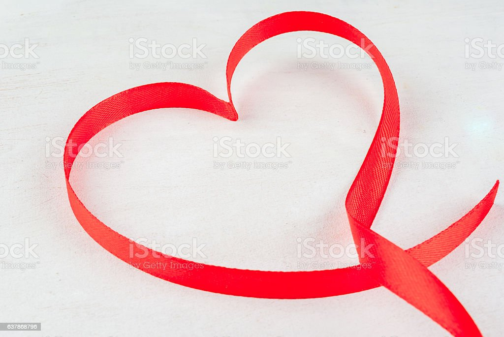 Red ribbon, lined in shape of heart stock photo