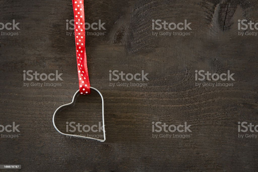 Red ribbon with heart shaped cookie cutter royalty-free stock photo