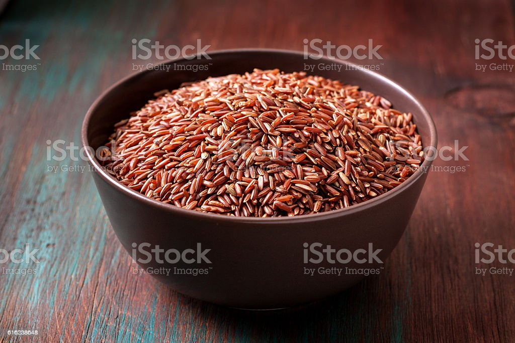 red rice in a ceramic bowl stock photo