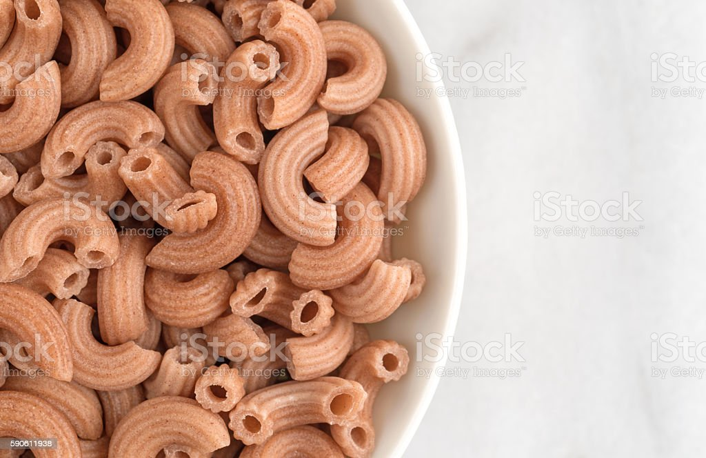 Red rice pasta elbows in bowl on marble cutting board stock photo