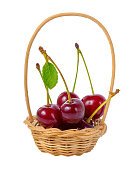 red ripe cherries with leaf in basket isolated on white