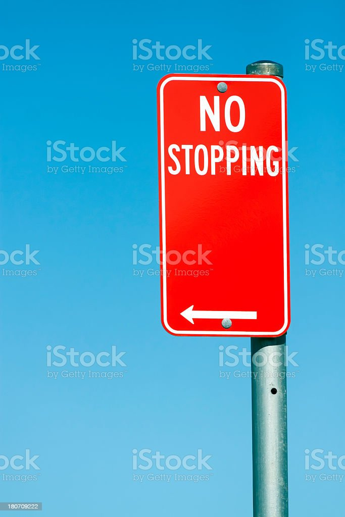 Red road sign 'NO STOPPING' against blue sky, copy space royalty-free stock photo