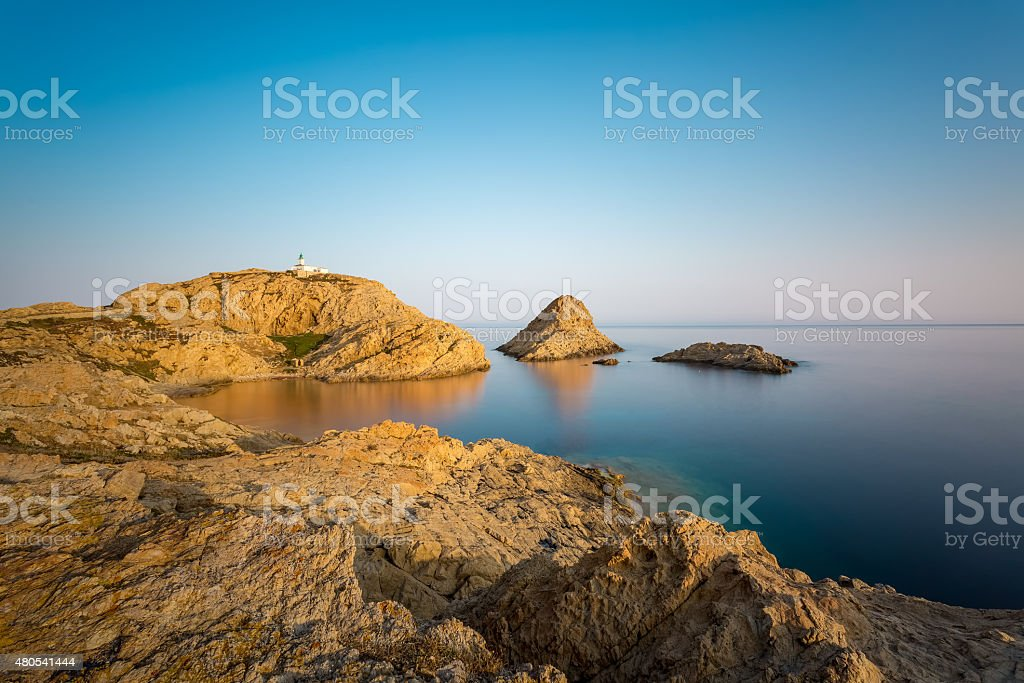 Red rocks and lighthouse of Ile Rousse in Corsica stock photo