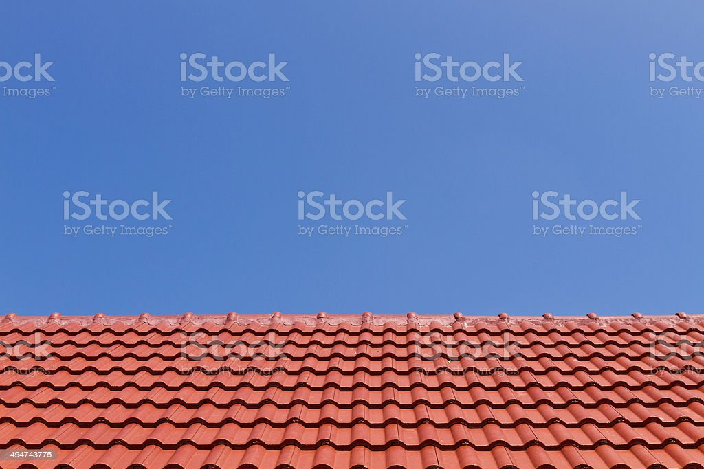 Red roof against blue sky stock photo