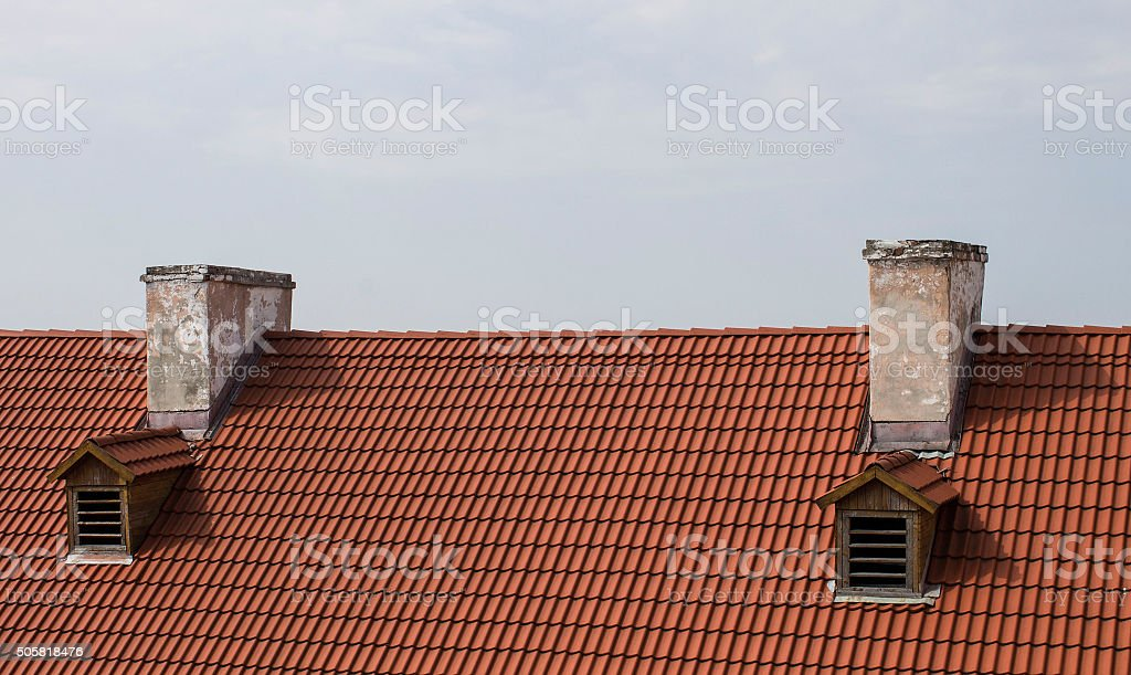 Red roof and two chimney against the sky stock photo
