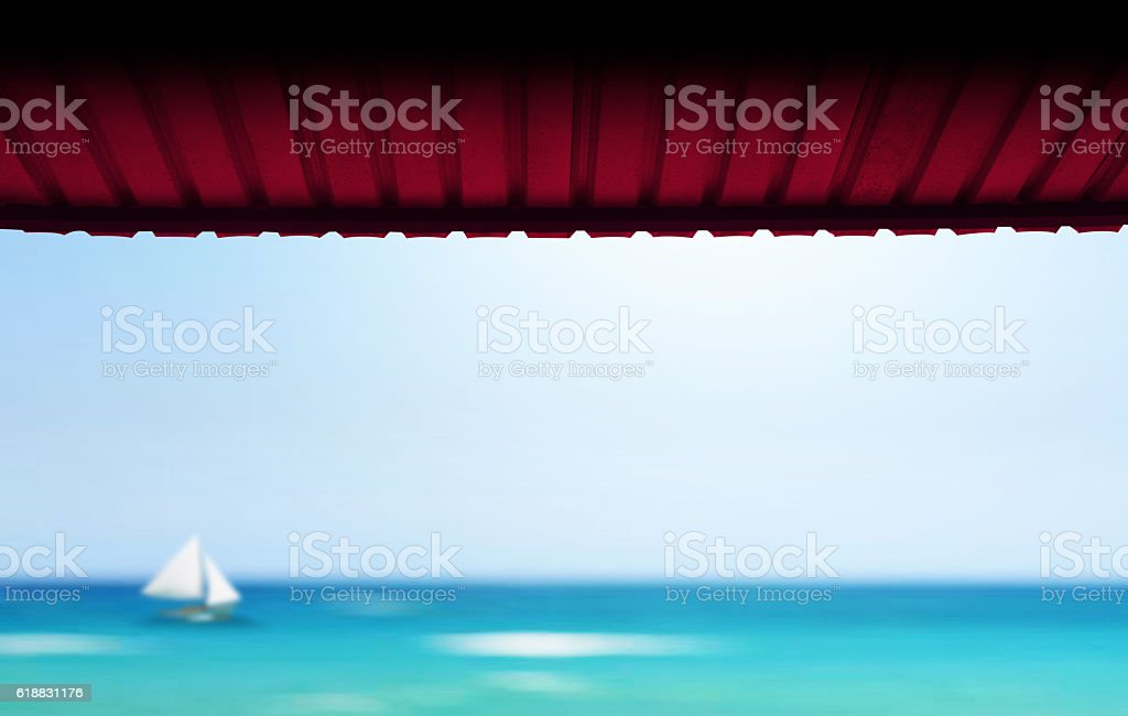 Red Roof at the blue sea beach with blurred sailboat stock photo