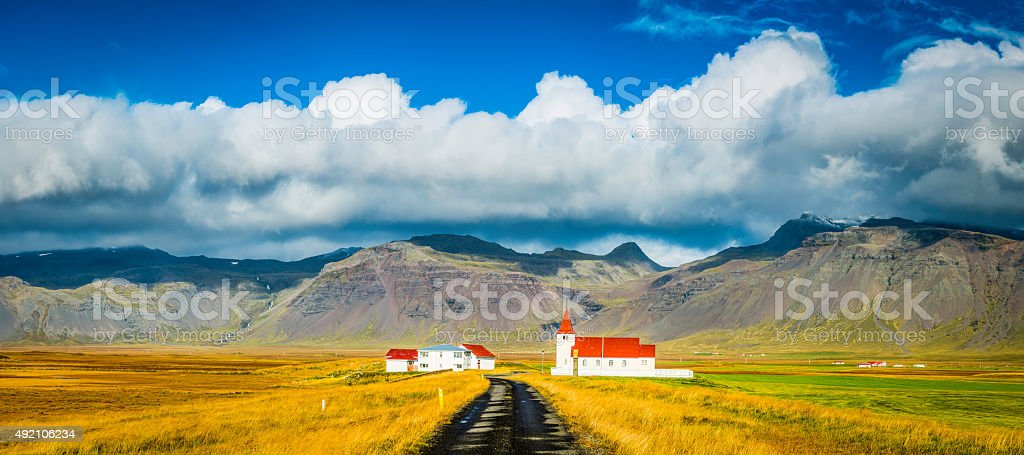 Red roof church and rural village farmhouses cloudscape panorama Iceland stock photo