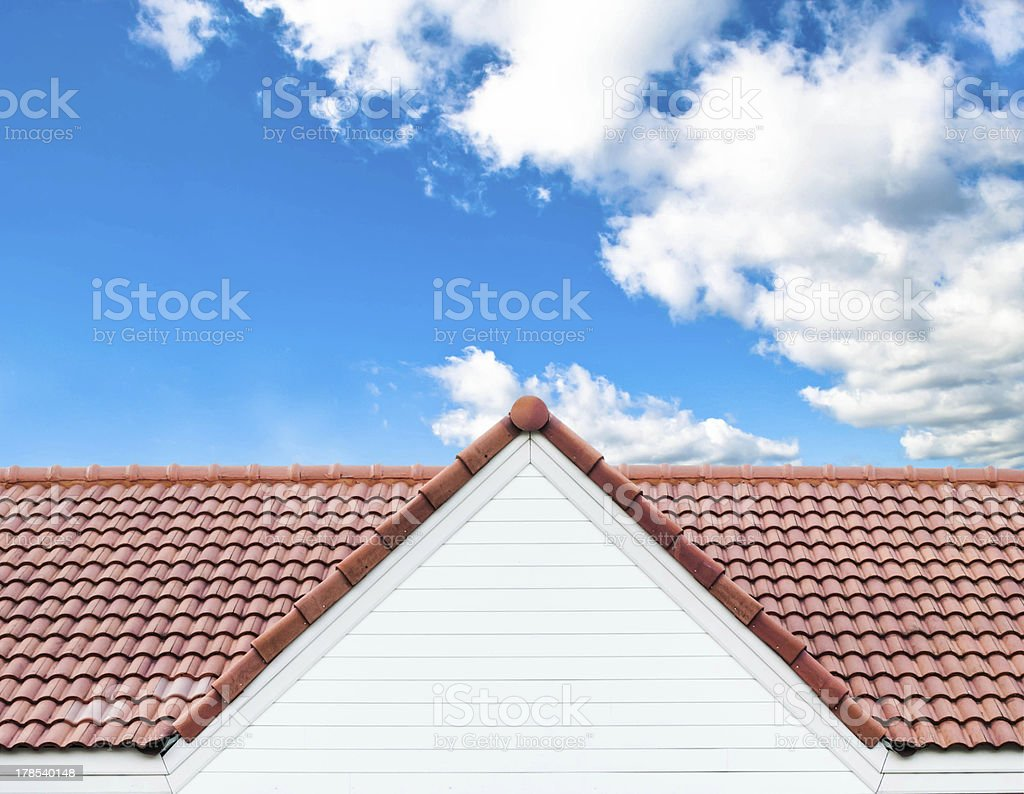 red rooftop against blue sky stock photo