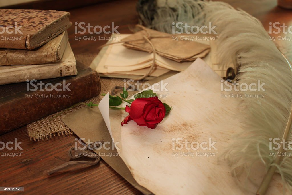 Red rose and beautiful quill on a vintage desk royalty-free stock photo