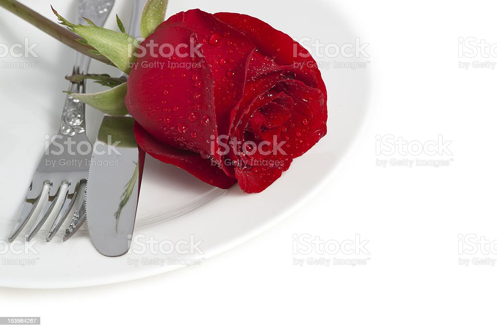 Red rose and cutlery on white plate royalty-free stock photo