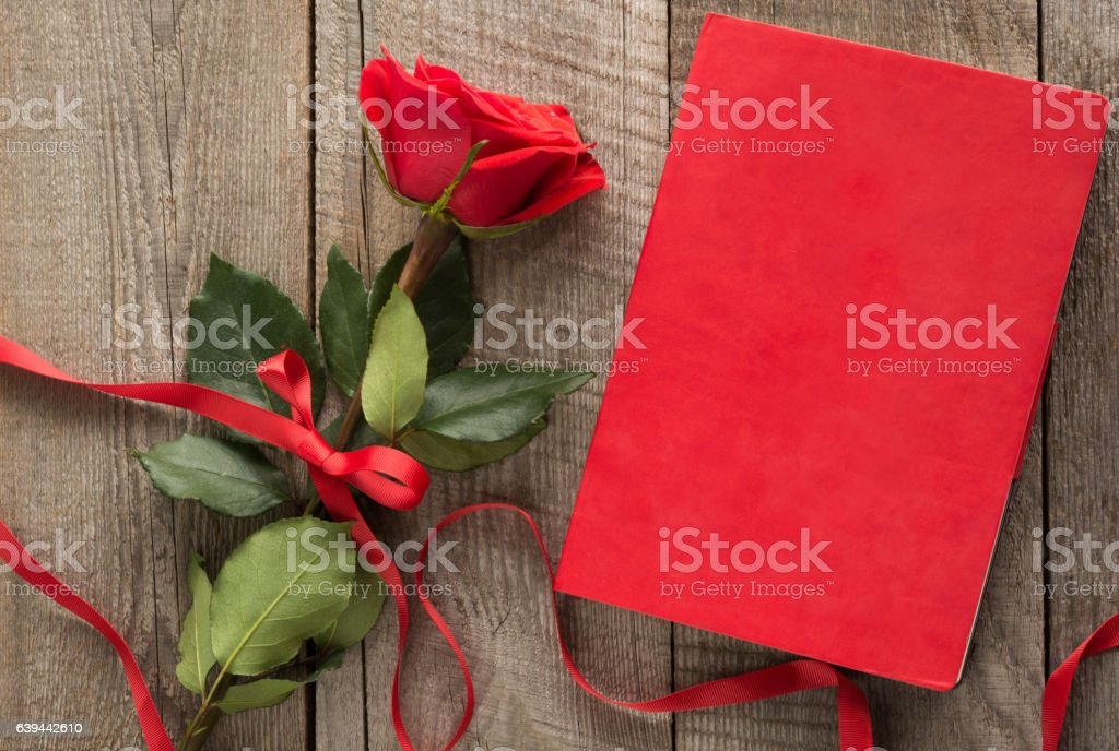 Red rose and red notebook on wooden board. Top view. stock photo