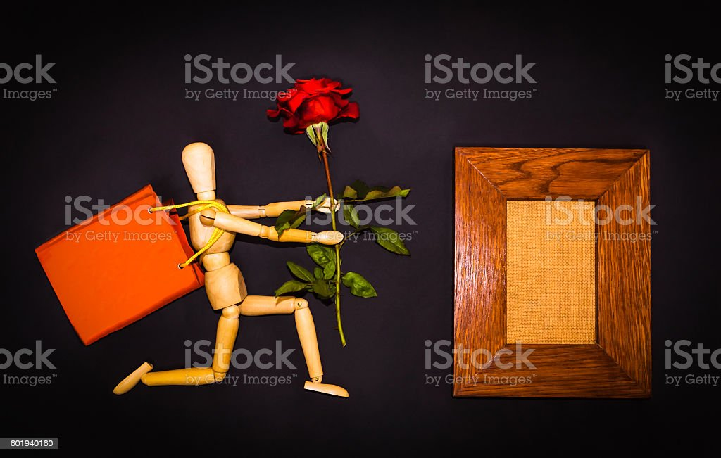 Red rose and wooden man on black background stock photo