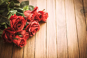 Red rose bouquet on vintage wood