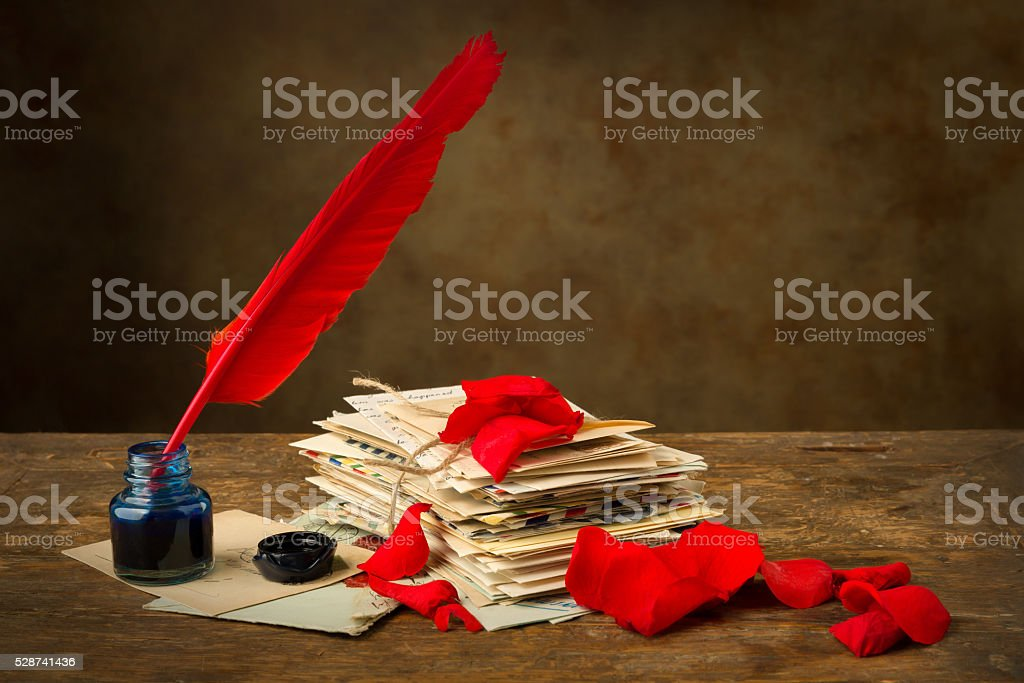 Red rose petals and antique letters stock photo