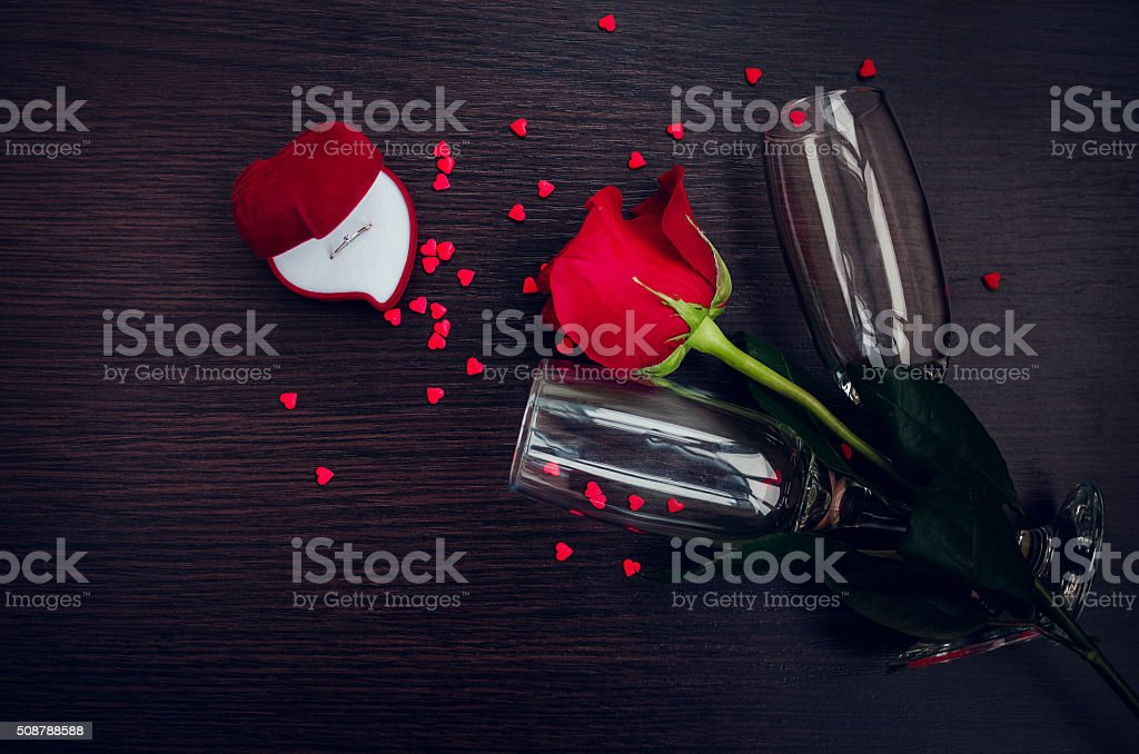 Red rose, ring, hearts and champagne glasses stock photo