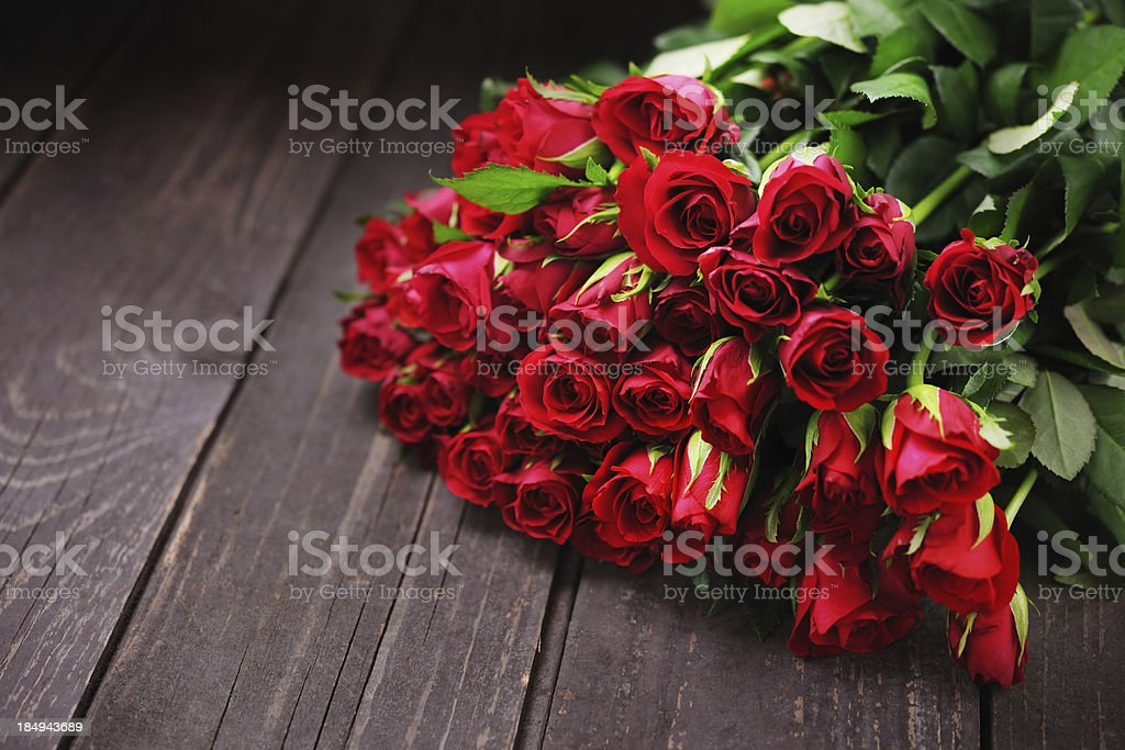 Red Roses on an old wooden table with copy space royalty-free stock photo