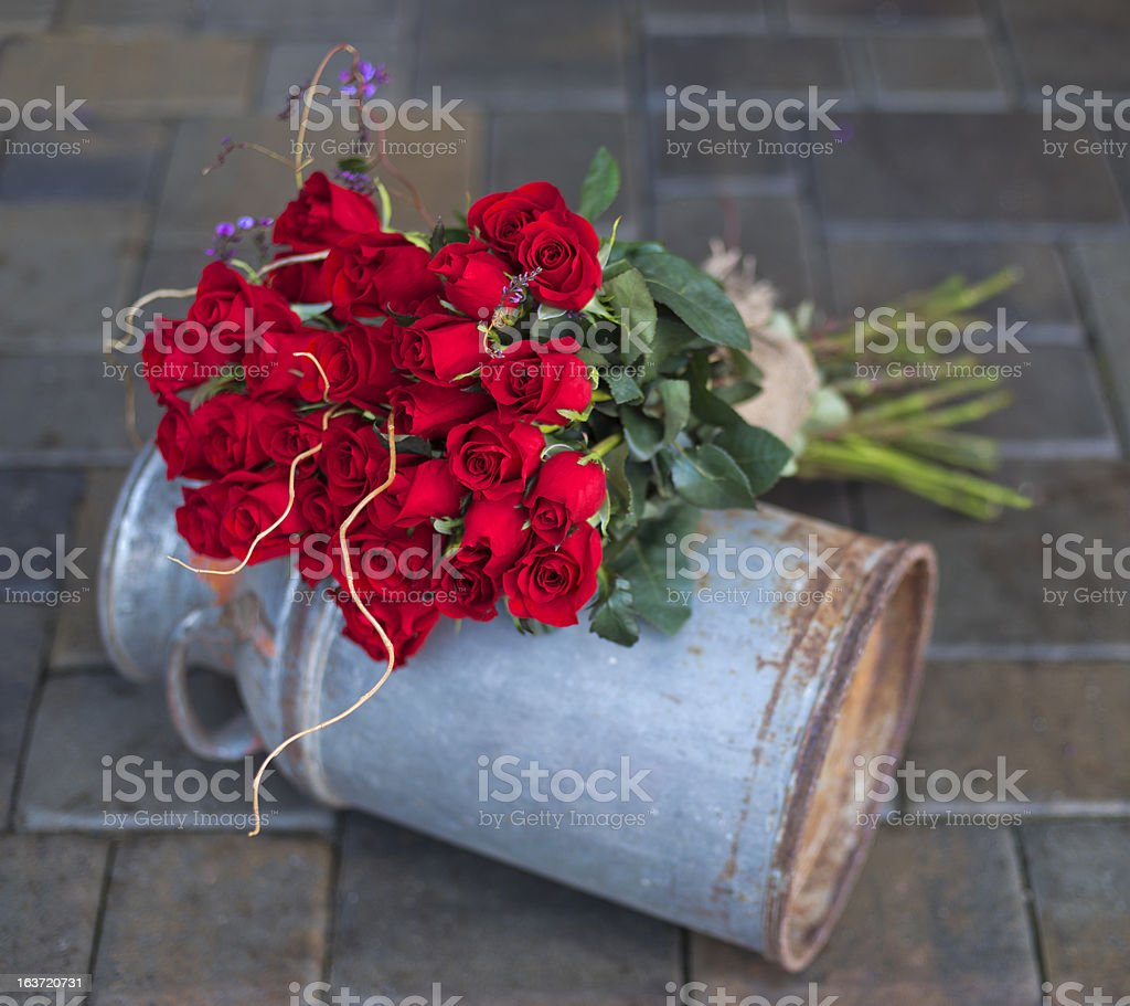 Red Roses Resting on a Vintage Milk Jug stock photo