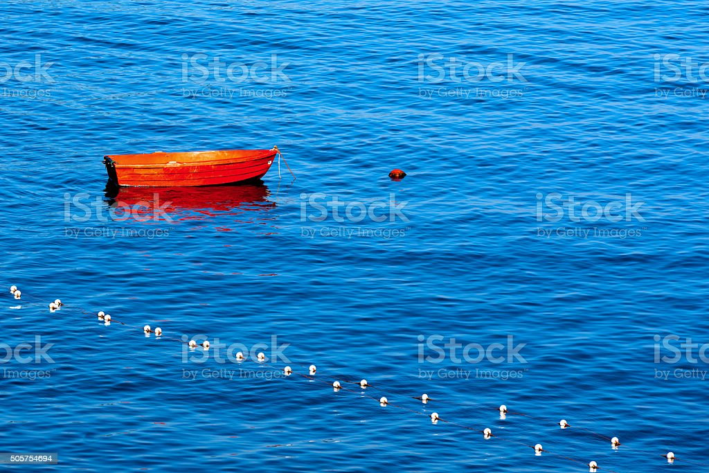 Red Row Boat Moored to Buoy stock photo