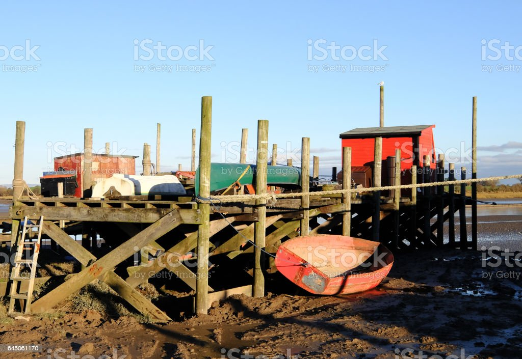 Red Row Boat Tied up at Wooden jetty stock photo