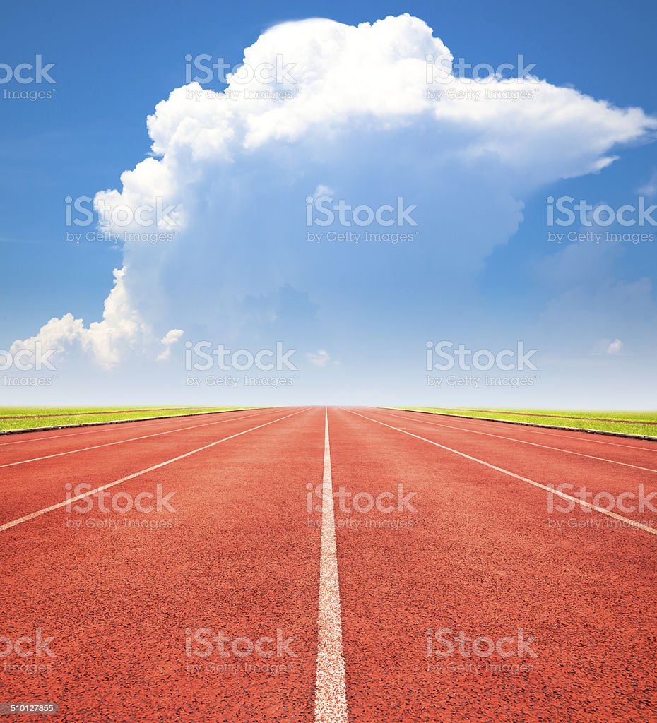 red running track over blue sky and clouds stock photo