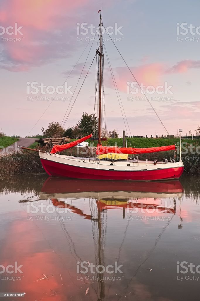 Red Sailing Boat in soft evening light stock photo