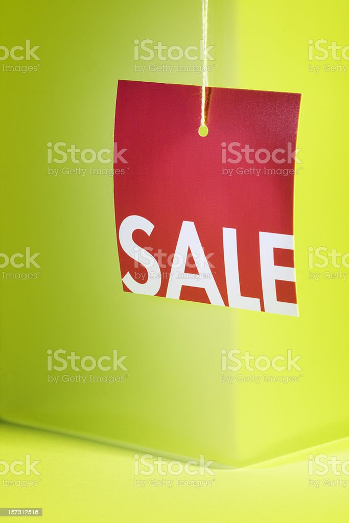 Red Sale Price Tag Sign Hanging Against Spring Green Background royalty-free stock photo