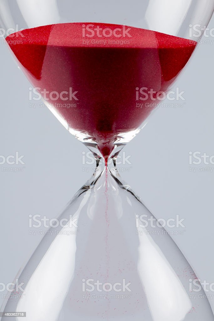 Red sand in an hourglass, vertical stock photo
