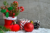 Red Santa's boot with fir tree branch,pine cone,gift.