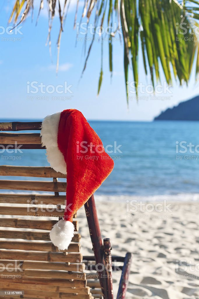 Red Santa's hat hanging on beach chair under palm tree royalty-free stock photo