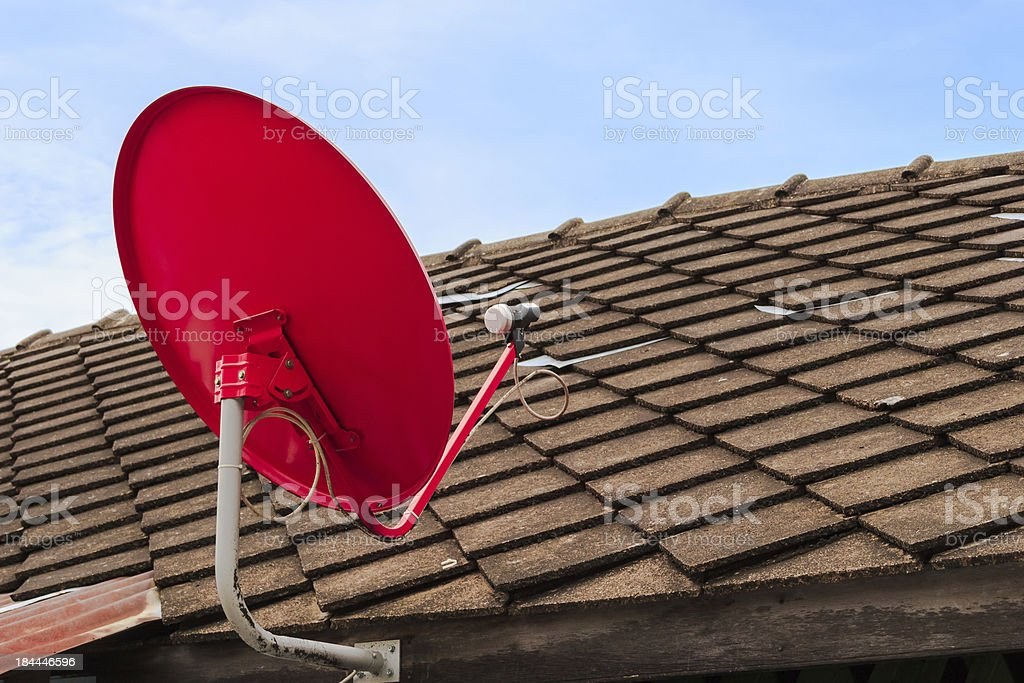 Red Satellite TV Receiver Dish on the Old Tiles Roof royalty-free stock photo