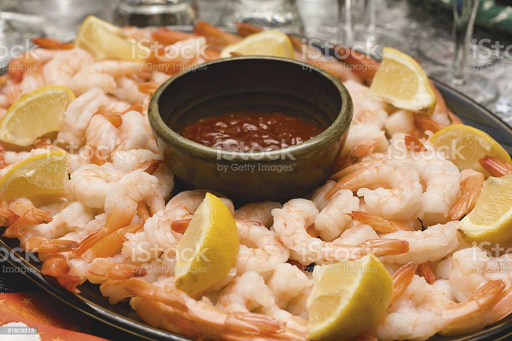 Red sauce in the middle of a shrimp platter with lemons stock photo
