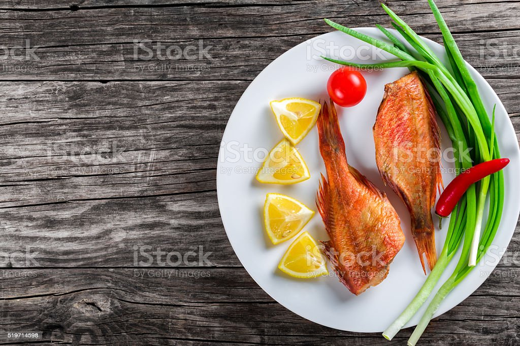 Red Sea Bass on white dish, top view stock photo