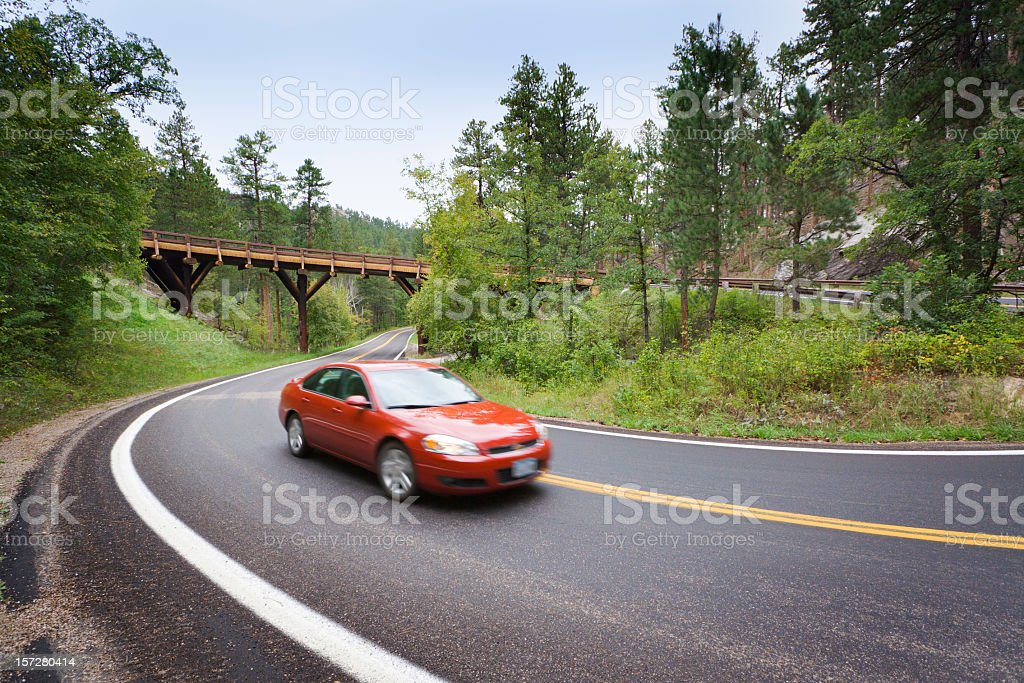 Red Sedan Car Driving Scenic Mountain Highway with Pigtail Bridge stock photo