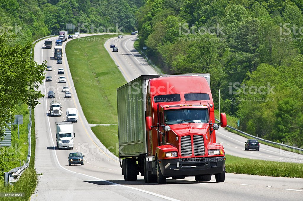 Red Semi Truck Climbing Hill On Interstate Highway royalty-free stock photo